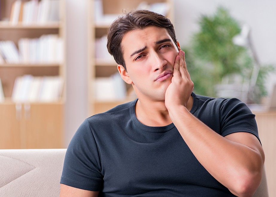 Man in need of emergency dentistry holding jaw in pain
