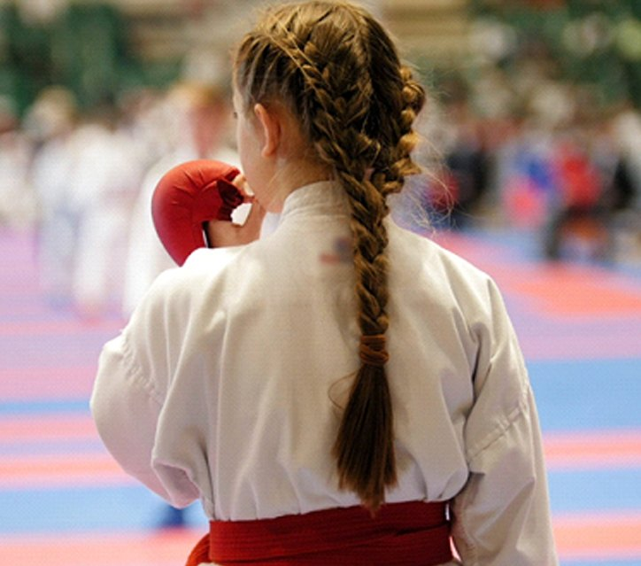 A young girl with her hair braided preparing to insert her mouthguard in San Antonio before engaging in a karate event