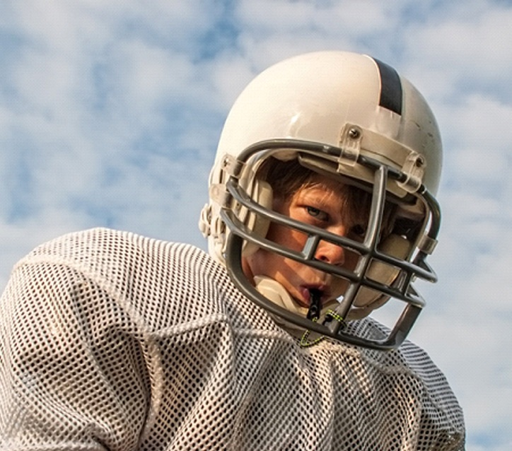 A young boy wearing football equipment and a mouthguard prepares to take the field