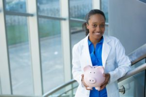 dentist smiling and holding pink piggy bank