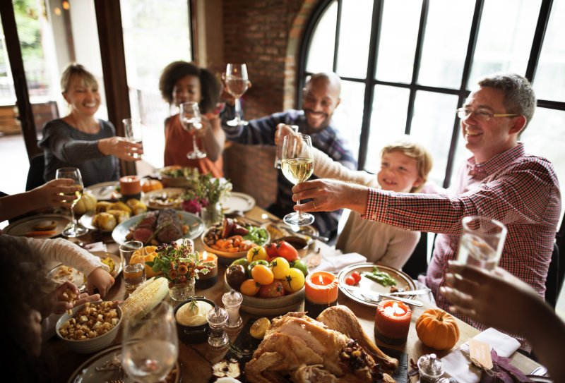 Friends cheers over Thanksgiving meal